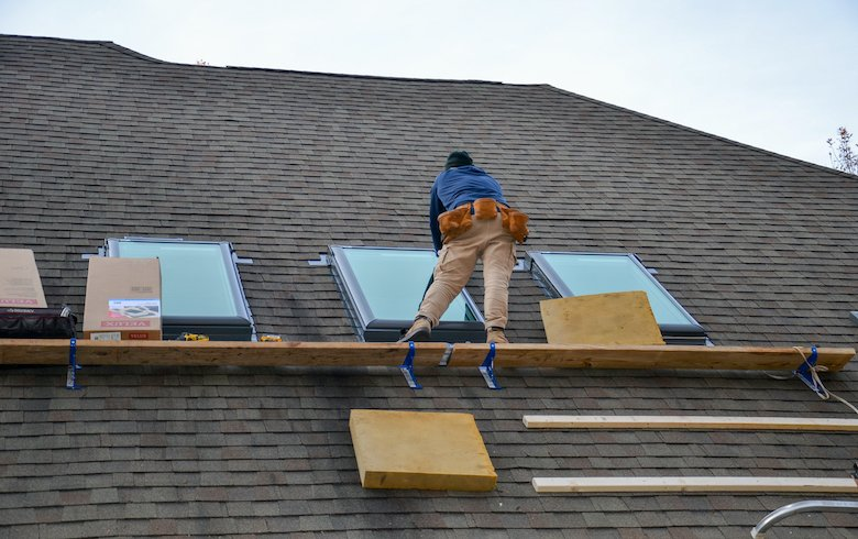 Roofer installing new skylights on a shingle roof