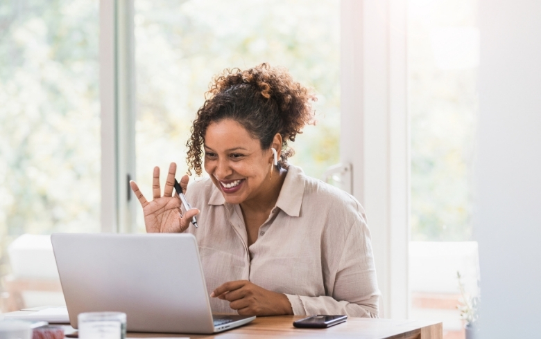 Virtual Consultation Blog Image of a Woman Smiling and Waving During a Virtual Meeting